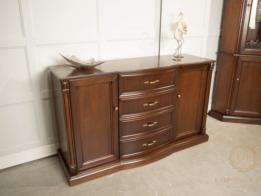 elegancka komoda z wypukłym środkiem, czterema szufladami łagodnie otwierającymi się. Drewniana, klasyczna komoda w kolorze brązowym idealna do salonu, pokoju lub gabinetu. Drewniana komoda z mosiężnymi uchwytaami w kolorze starego złota, z bocznymi drzwiczkami, półkami, na cokole z pieknym blatem drewnianym w półmacie