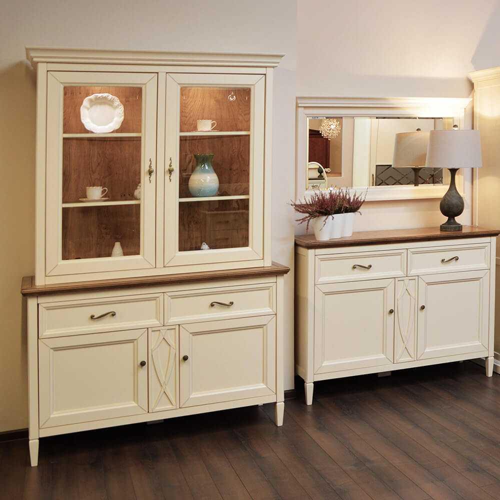 przeszklona witryna prowansja z oświetleniem, komoda z szufladami na nóżkach nad wiszące lustro w drewnianej ramie